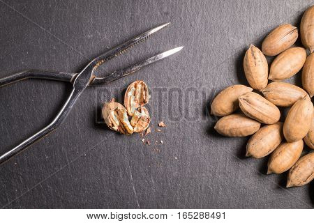 Pecans with nutcracker on slate stone and a broken walnut