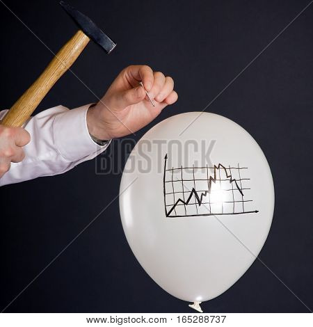 businessman hitting a nail into a white balloon with a decaying financial chart