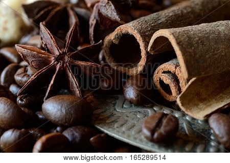 Closeup of coffee beans, anise and cinnamon sticks, food background with horizontal composition