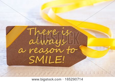 Label With English Quote There Is Always A Reason To Smile. White Wooden Background. Card For Seasons Greetings Or Easter Greetings