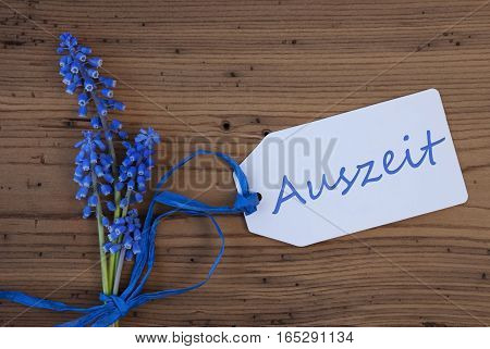 Label With German Text Auszeit Means Downtime. Blue Spring Grape Hyacinth With Ribbon. Aged, Rustic Wodden Background. Greeting Card For Spring Season