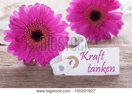 Label With German Text Kraft Tanken Means Relax. Pink Spring Gerbera Blossom. Vintage, Rutic Or Aged Wooden Background. Card For Spring Greetings.