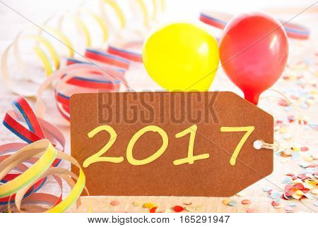 One Label With Text 2017 For Happy New Year Greetings. Party Decoration Like Streamer, Confetti And Balloons. Wooden Background With Vintage, Retro Or Rustic Syle