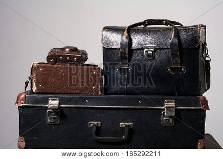 Stack Of Old Shabby Suitcase With A Camera In Bag