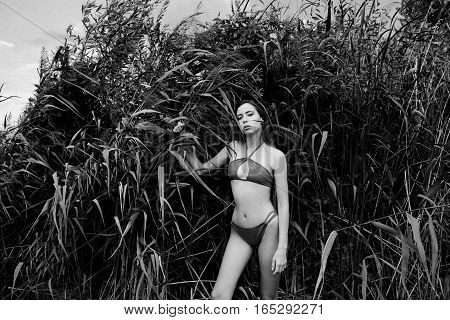 Young girl with long dark hair in red swimsuit posing outdoors in the reeds. Summer photo concept