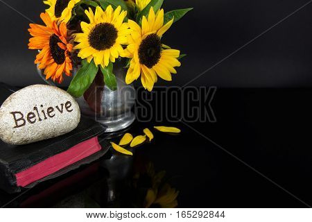 word believe carved in stone on Holy Bible with sunflowers in pewter pitcher