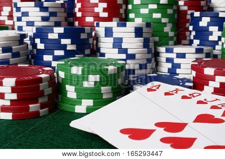 A close up image of stacked poker chips and a royal flush poker hand.