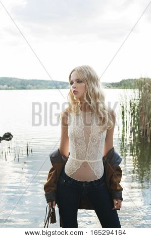Beautiful blonde woman wearing flared jeans a white lace top and a brown jacket posing on the lake. Hippie Boho Style. Baby's face model
