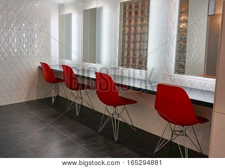 Mirrors, desk and red chairs on dressing room