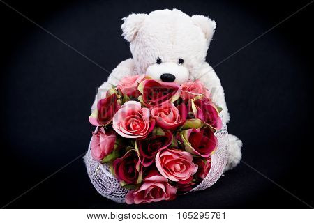 Selective focus at bouquet of beautiful artificial red roses in the arms of blurry white bear doll on black background concept love for valentine day or spacial anniversary