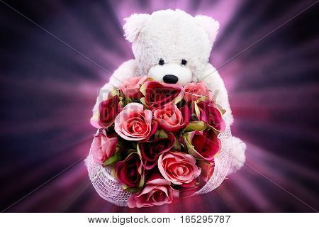 Selective focus at bouquet of beautiful artificial red roses in the arms of blurry bear doll on black background and pink ray light effect concept love for valentine day or spacial anniversary