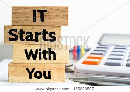 Text message It starts with you on wooden with office table. Business concept