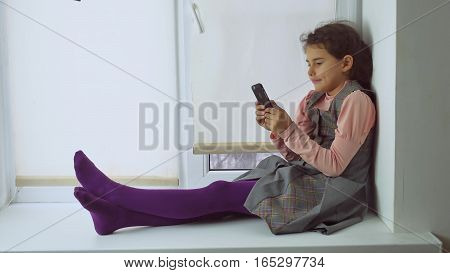 teen girl sitting on window sill plays the online game for web smartphone