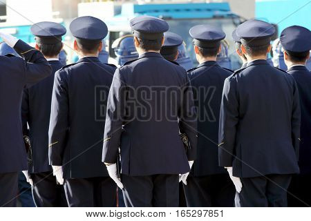 Back view of Japanese police officers stand in a row