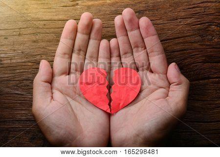 man holding a paper broken heart on wooden background