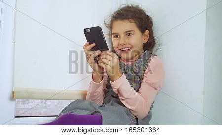 teen girl sitting on window web sill plays the online game for smartphone