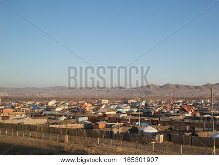 The outskirts of Ulan Bator, Mongolia showing houses and yurts  or gers which are traditional nomadic homes. The photograph is taken through the window of a train car on the Trans-Siberian Railway. Deep blue sky is above and mountainsee in the distance.