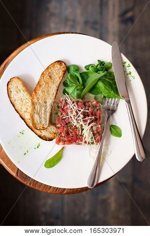 Tartare of beef with spinach on a white plate. Isolated on black or dark wooden background.