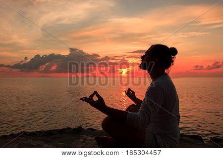 Yoga scene man silhouette in sunset background.