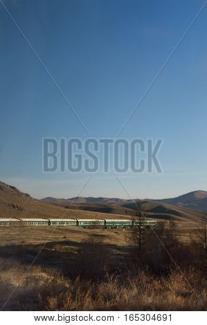 The last six cars of the Trans-Siberian Railway train on an ess curve photographed through the window of a forward car. Mountains and deep sky are in the background and dried grass and vegetation are in the shadows of the train in the foreground.