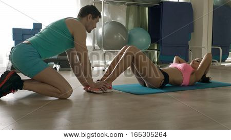 Woman doing abdominal crunches press exercise on the mat with her sports male trainer in gym. fitness, sport, training, gym and lifestyle concept. Personal trainer helping woman working.