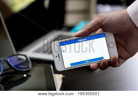 Bangkok, Thailand - December 5, 2016: Business man is logging in to Facebook on his phone.
