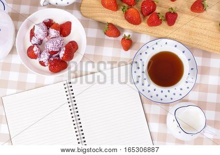 Strawberries and cream with blank recipe book on a chopping board