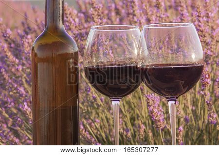 A macro photo of a bottle and two glasses of red wine in a lavender field. Toned image