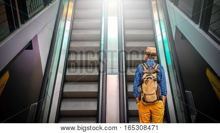 the unidentified tourist with backpack going up escalator