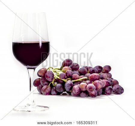 A photo of a glass of red wine with a bunch of grapes, shot from the side on white background