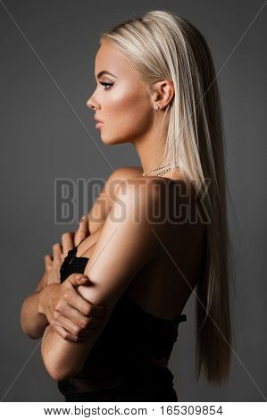 hairstyle, haircare and fashion concept - natural blond woman profile portrait with beautiful hair on grey background