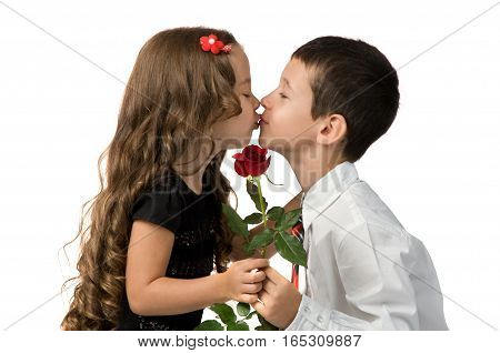 relationship between young children. boy gives a girl flowers. boy kisses a girl