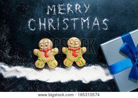 Baking Gingerbread Men for Christmas on dark table winter snow night