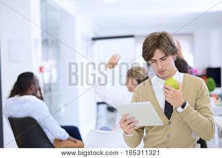 Portrait of confident young businessman using digital tablet while colleague in background