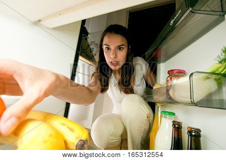 a beautiful woman is grabbing a snack from her fridge.