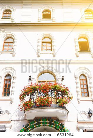 Facade of an architectural building with flowering balcony
