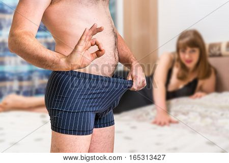 Woman In Bed And Man In Underwear Showing Ok Gesture