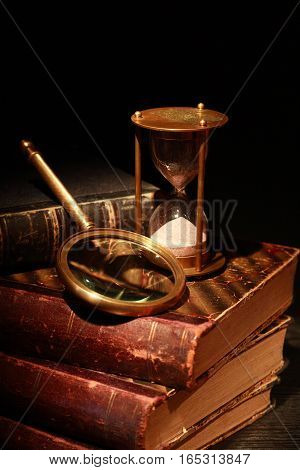 Vintage still life. Magnifying glass and hourglass near old book