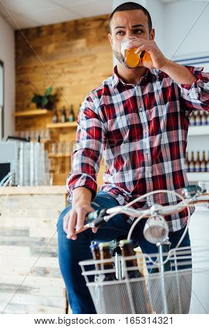 Portrait of stylish man drinking light craft beer while sitting on bicycle