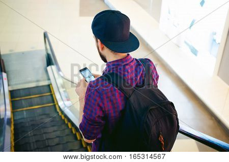 Young Man With A Beard In A Plaid Shirt And A Tie And Cap, Riding On An Escalator In The Mall, Looki