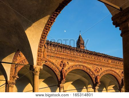 Grand Cloister of the Certosa di Pavia monasteryfeatures columns with precious decorations in terracotta portraying saints prophets and angels in white and pink Verona marbleat sunsetItaly.
