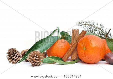 clementines with leaf and cinnamon on white background