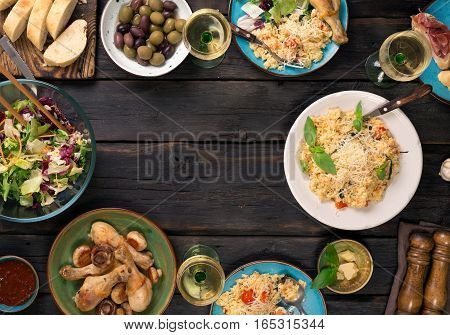 Frame of risotto with tomatoes and parmesan cheese salad appetizer chicken drumsticks and wine. Italian food dark background
