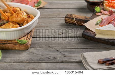 Baked chicken drumsticks with a variety of snacks on a wooden table with a free place