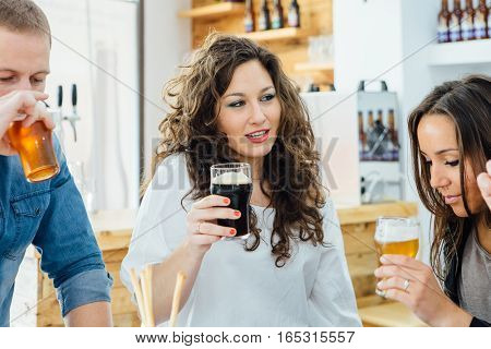 Beautiful woman with curly hair tasting dark craft beer