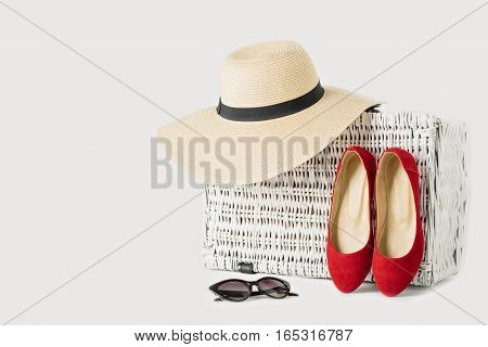 White wicker suitcase women's hat sunglasses and red shoes