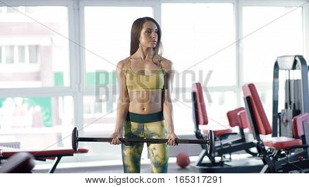 Woman exercising with barbell in gym. Brunette during workout in gym. Girl is beautiful sportswear. Young woman is preparing for the exercises.