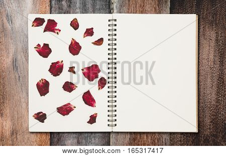 Press dried rose petals, photo album with copy space, on wood texture