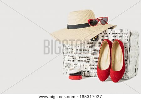 White wicker suitcase women's hat bracelets sunglasses and red shoes