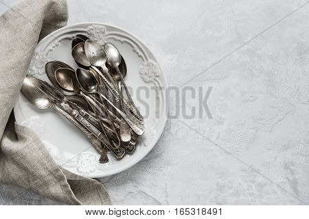 Various silverware on a ceramic plate on the background of gray concrete surface with copy-space